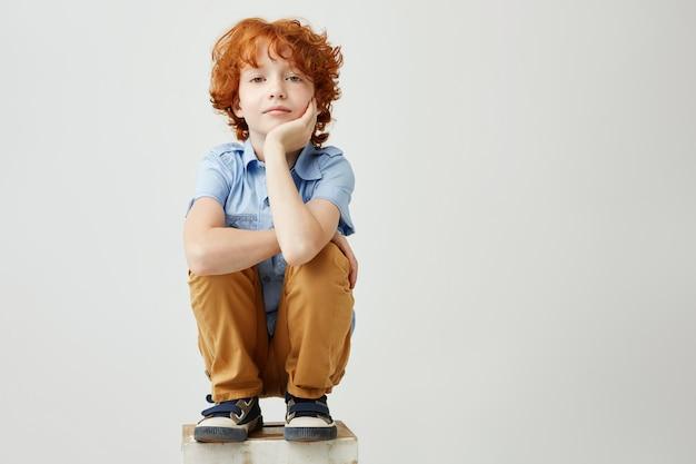 Śmieszny rudzielec mały chłopiec siedzi na pudełku, trzyma głowę ręką