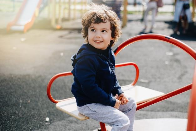 Śmieszny śliczny szczęśliwy dziecko bawić się na boisku. emocja szczęścia, zabawy, radości. uśmiech dziecka