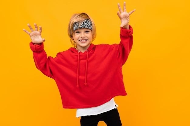 Śmieszny śmieszny facet w czerwieni ubraniach na żółtym tła ono uśmiecha się