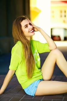 Śmieszny stylowy seksowny uśmiechnięty piękny młoda kobieta model w lato jaskrawym żółtym modnisia sukiennym obsiadaniu na ulicy