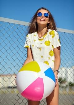 Śmieszny szalony splendor elegancki uśmiechnięty piękny młoda kobieta model w jaskrawego modnisia lata przypadkowych ubraniach pozuje na ulicie za żelazną kratownicą i niebieskim niebem. zabawa z kolorową dmuchaną kulą