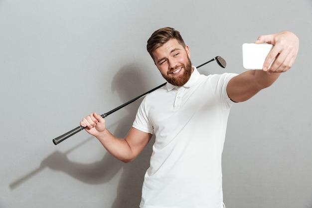 Śmieszny szczęśliwy golfista robi selfie na jego smartphone