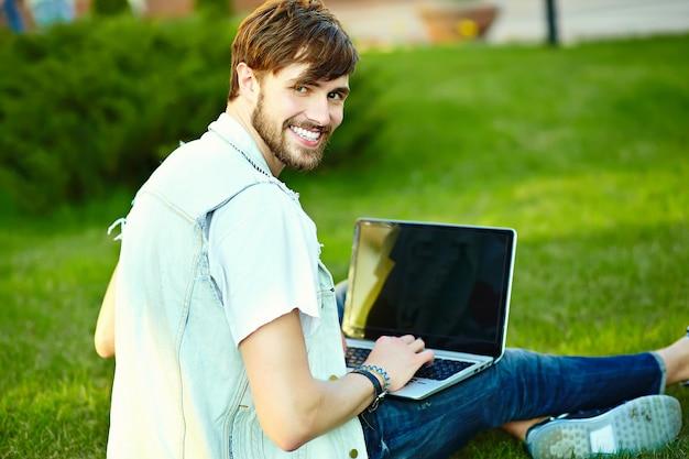 Śmieszny uśmiechnięty modnisia przystojny mężczyzna facet w eleganckim lata płótnie w trawie z notatnikiem