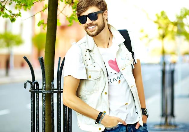 Śmieszny uśmiechnięty modnisia przystojny mężczyzna facet w stylowych lat ubraniach chodzi na ulicie pozuje w okularach przeciwsłonecznych