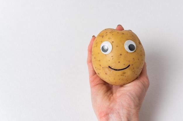 Śmieszny ziemniak z oczami i namalowanym uśmiechem jest na dłoni na białym tle.