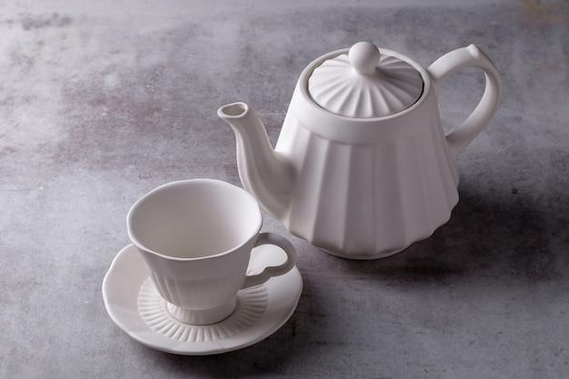 Śmietanka do herbaty, filiżanka i spodek na płycie cementowej