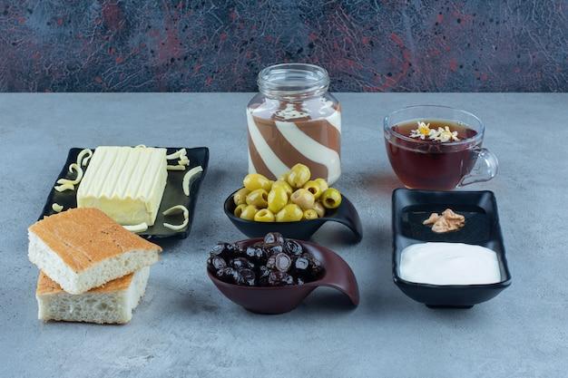 Śmietanka, miód, czekolada, pieczywo, ser, czarne i zielone oliwki oraz filiżanka herbaty na marmurowym stole.