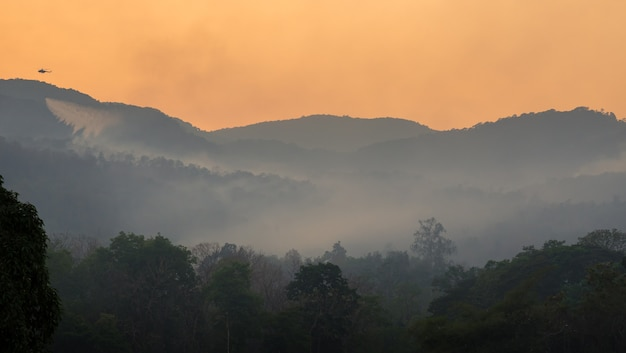 Śmigłowiec służb ratowniczych upuszcza wodę, aby ugasić pożary lasów, które spłonęły w górach.