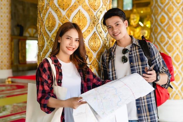 Smiley azjatycka para turystów z plecakami stojących w pięknej tajskiej świątyni, ładna kobieta trzymająca papierową mapę i przystojny mężczyzna zameldować się w smartfonie z szczęśliwym na wakacjach