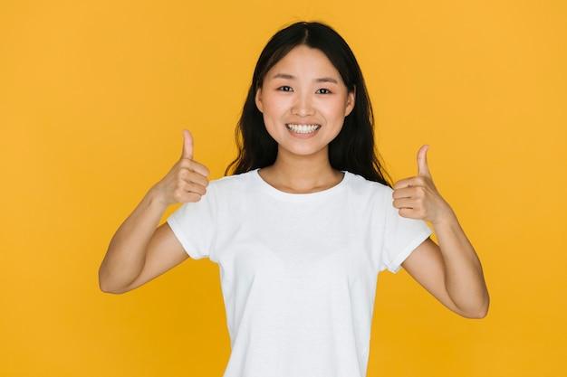 Smiley azjatykcia kobieta daje jej zatwierdzeniu