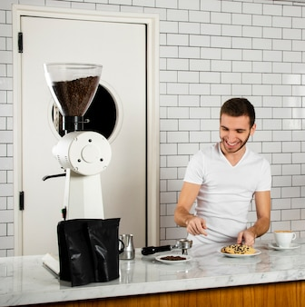 Smiley barista za ladą w kawiarni