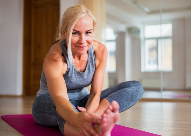 Smiley blond kobieta robi pilates