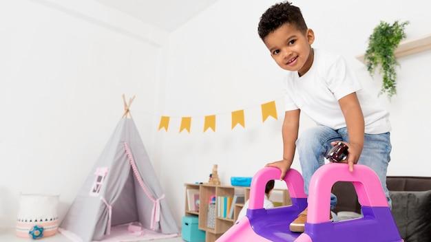 Smiley boy gry ze zjeżdżalnią w domu