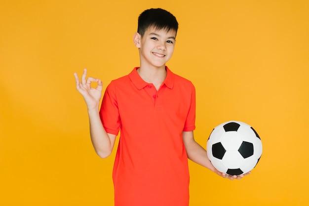 Smiley chłopiec trzyma futbolową piłkę