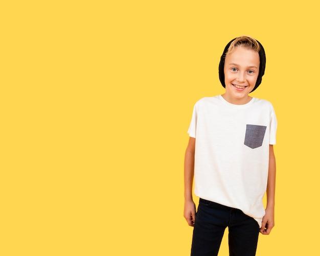 Smiley chłopiec ubierał przypadkowego na żółtym tle