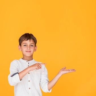 Smiley chłopiec wskazuje w jeden kierunku z kopii przestrzenią