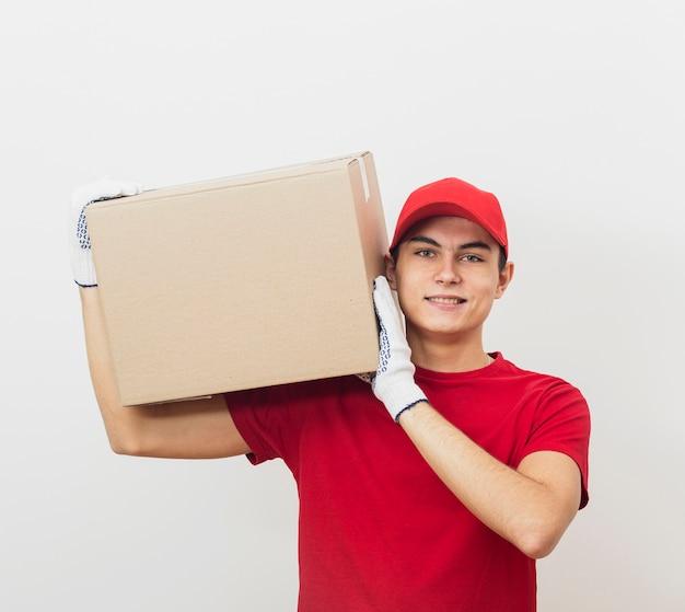 Smiley człowiek dostawy niosąc pudełko