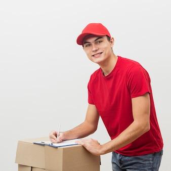 Smiley człowiek dostawy podpisywania dokumentów
