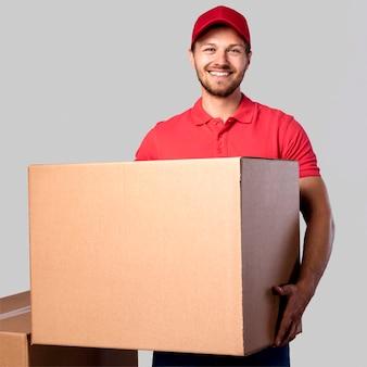Smiley człowiek dostawy z pudełkiem