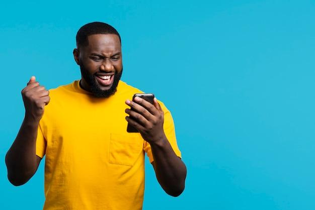 Smiley człowiek patrząc na telefon komórkowy
