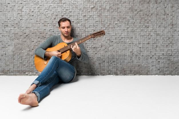 Smiley człowiek siedzi na podłodze i gra w dal