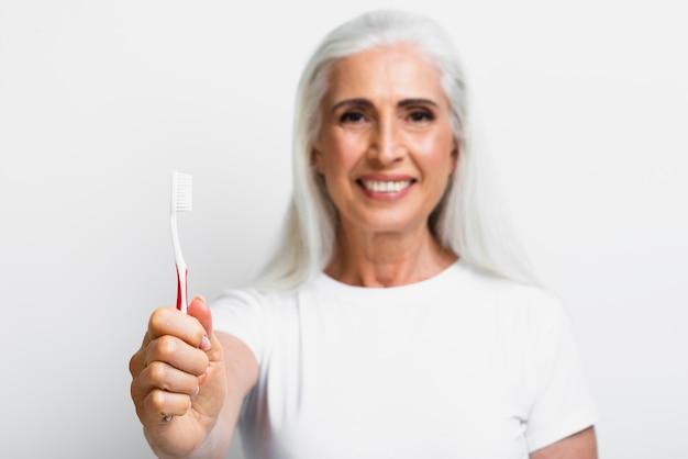 Smiley dojrzała kobieta dumna ze swojej szczoteczki do zębów