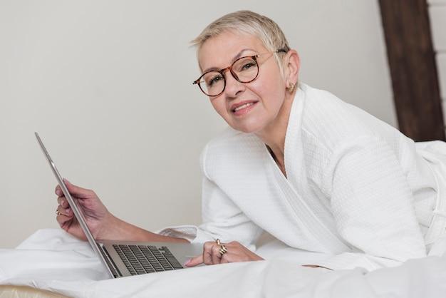 Smiley dojrzała kobieta używa laptop w łóżku