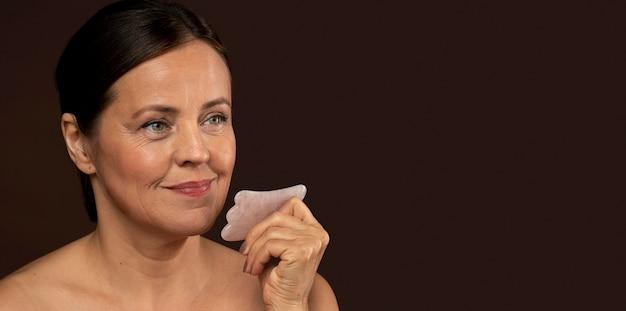 Smiley dojrzała kobieta za pomocą rzeźbiarza twarzy kwarcu różowego z miejsca na kopię