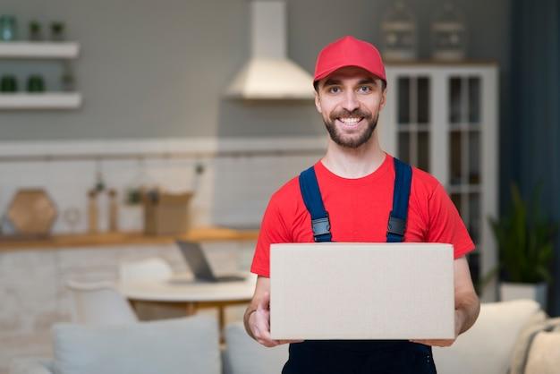 Smiley doręczeniowy mężczyzna pozuje podczas gdy trzymający pudełko
