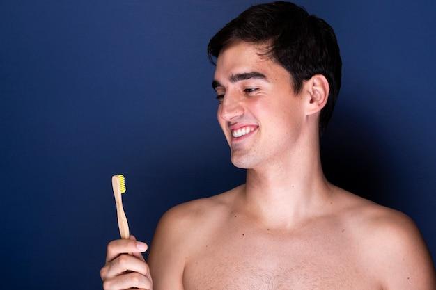 Smiley dorosły mężczyzna trzyma szczoteczkę do zębów