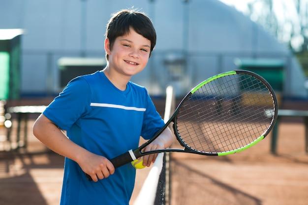 Smiley dzieciak odpoczywa na tenisowej sieci