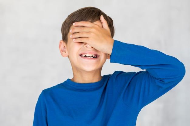Smiley dzieciak zakrywający oczy