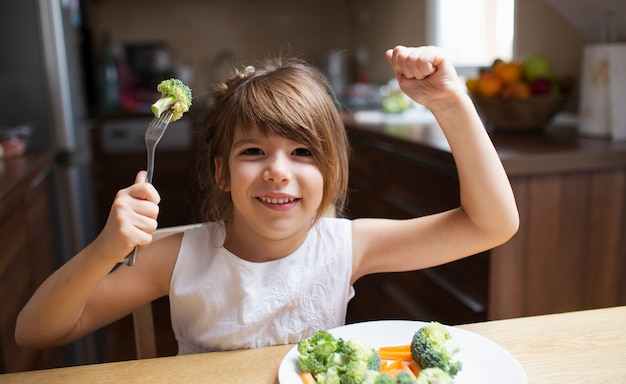 Smiley dziewczyna bawi sie z jedzeniem