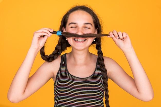Smiley dziewczyna bawić się z jej warkoczami