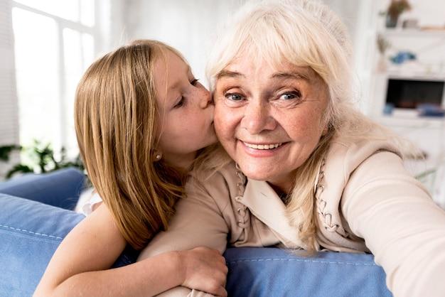 Smiley dziewczyna całuje babcię