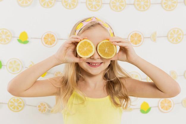 Smiley dziewczyna pozuje podczas gdy zakrywający oczy z cytryna plasterkami