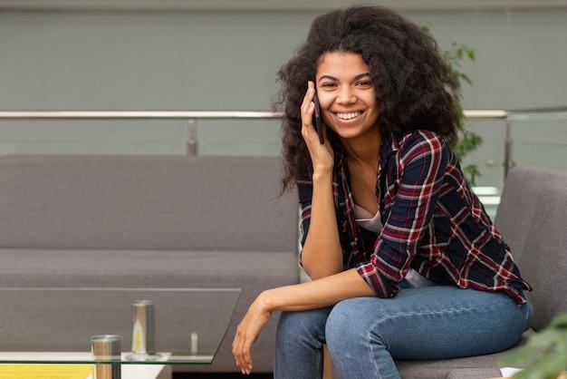 Smiley dziewczyna w bibliotece rozmawia przez telefon
