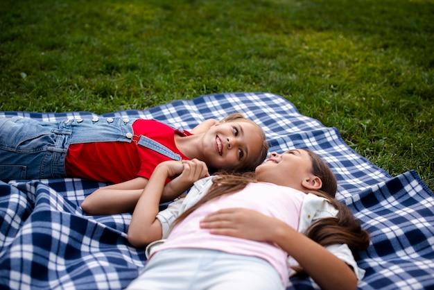 Smiley dziewczyny na koc, trzymając się za ręce razem
