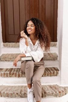 Smiley kędzierzawa kobieta trzyma książkę