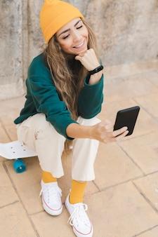 Smiley kobieta bierze selfie podczas gdy siedzący na deskorolka