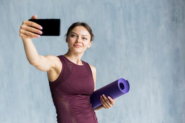 Smiley kobieta bierze selfie podczas gdy trenujący