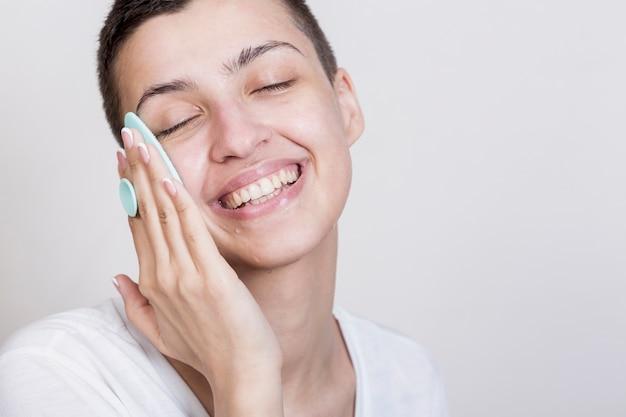 Smiley kobieta czyszczenia procesu twarzy