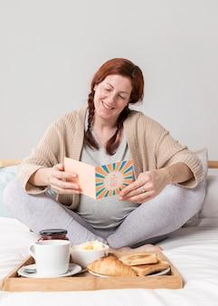 Smiley kobieta czytająca kartkę z życzeniami