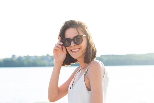 Smiley kobieta jest ubranym okulary przeciwsłonecznych