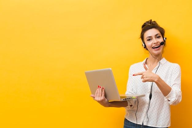Smiley kobieta ma na sobie słuchawki i wskazując na laptopa, który trzyma