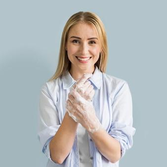 Smiley kobieta myje jej ręce mydłem