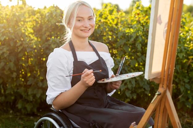 Smiley kobieta na wózku inwalidzkim na zewnątrz w przyrodzie z paletą i płótnem