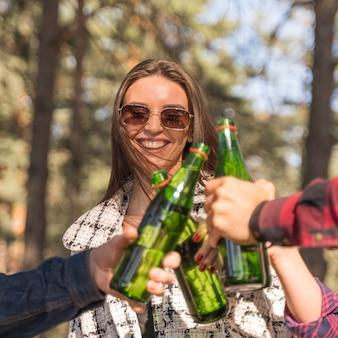 Smiley kobieta opiekania piwa z przyjaciółmi na zewnątrz