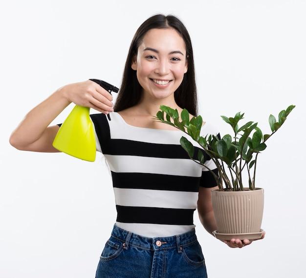 Smiley kobieta opryskiwanie kwiatów liści
