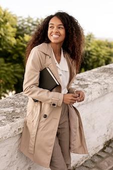 Smiley kobieta patrzeje oddalony podczas gdy trzymający książkę